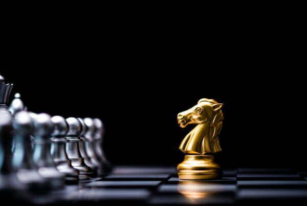 Goldener Pferdeschach trifft auf silberner Schachfeind auf Schachbrett und schwarzem Hintergrund. Konzept des Marktwettbewerbs oder des Unternehmens.